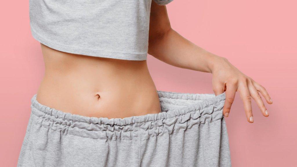 年輕人女士穿著她的舊衣服表明她減去了多少重量。